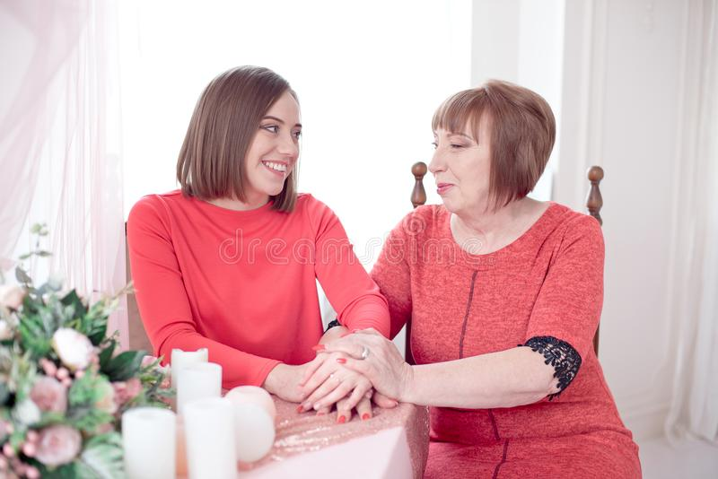 Dojrzały matki I córki mienie wręcza być usytuowanym przy stołem obraz stock