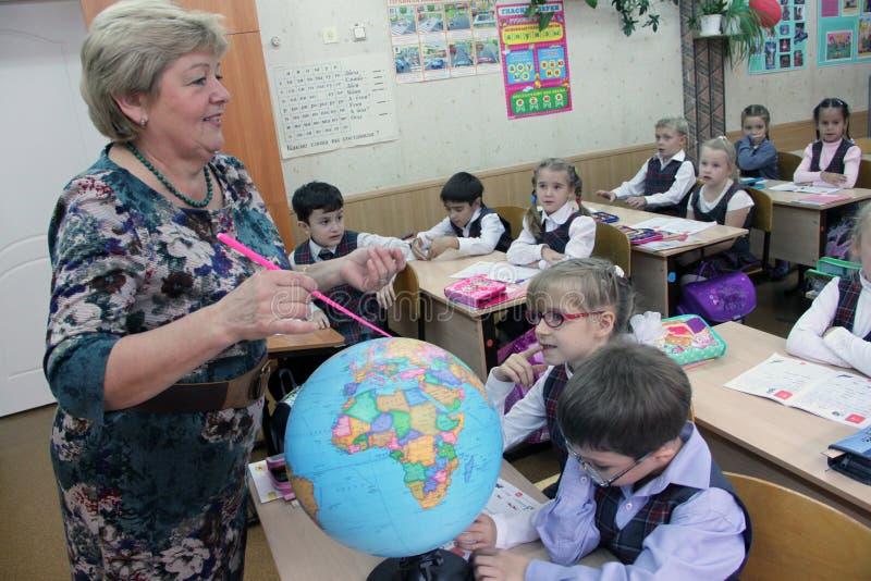 Dojrzały nauczyciel pokazuje kulę ziemską dzieci obraz royalty free