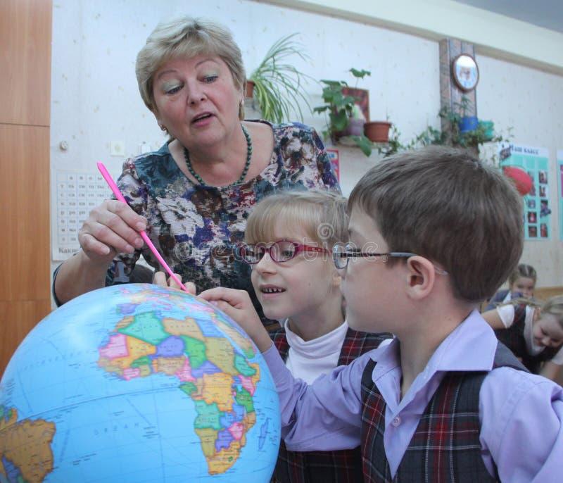 Dojrzały nauczyciel pokazuje kulę ziemską dzieci fotografia royalty free