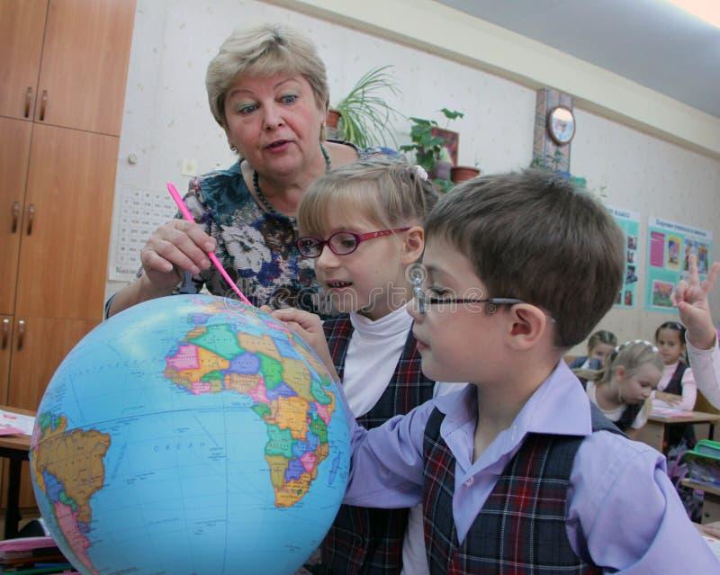 Dojrzały nauczyciel pokazuje kulę ziemską dzieci zdjęcie royalty free