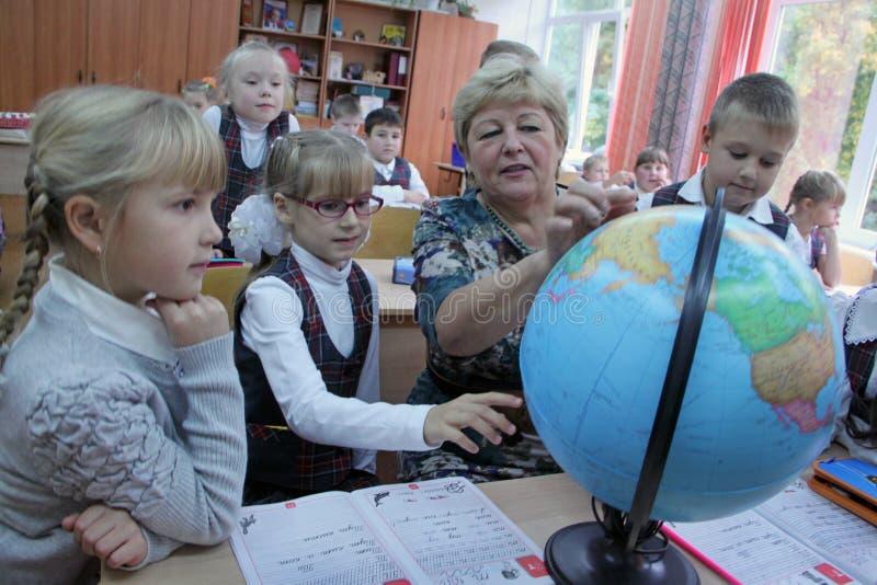 Dojrzały nauczyciel pokazuje kulę ziemską dzieci zdjęcia royalty free