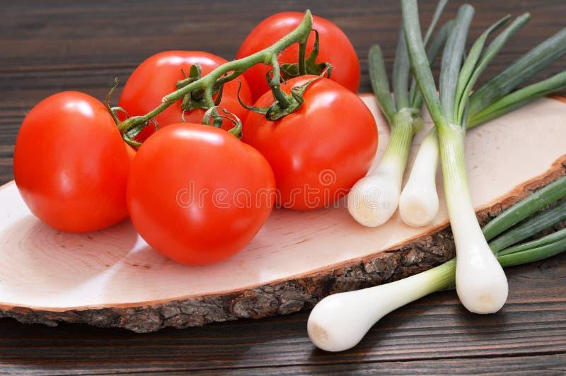 Dojrzały pomidorowy grono i zielone cebule obrazy stock