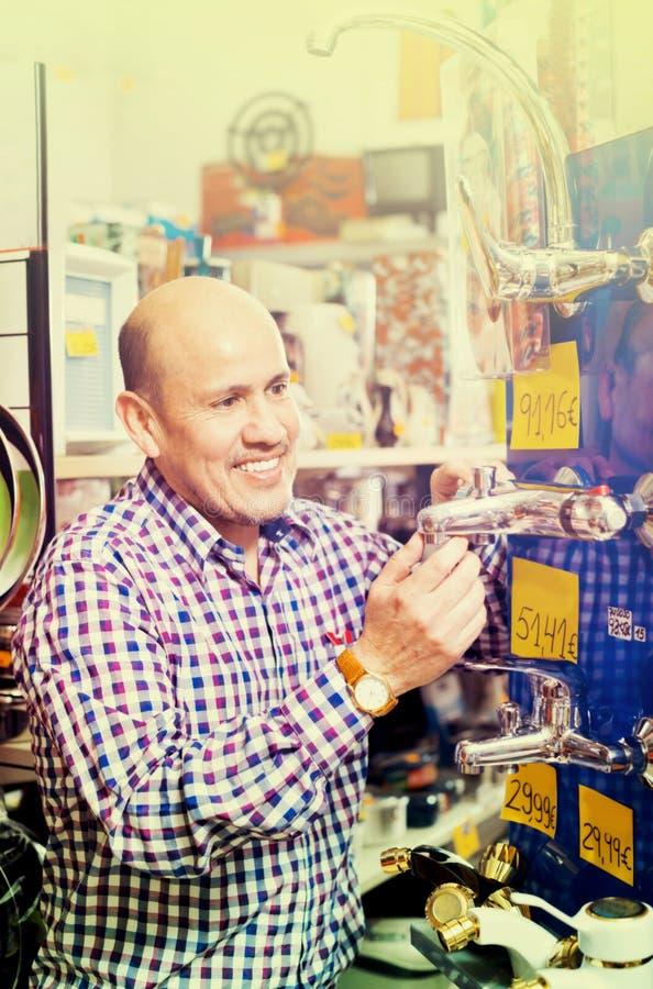 Dojrzały pozytywny mężczyzna wybiera grzejnego wodnego klepnięcie w sklepie zdjęcie royalty free