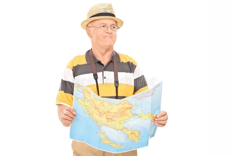 Dojrzały turystyczny odprowadzenie z mapą w jego ręki fotografia royalty free