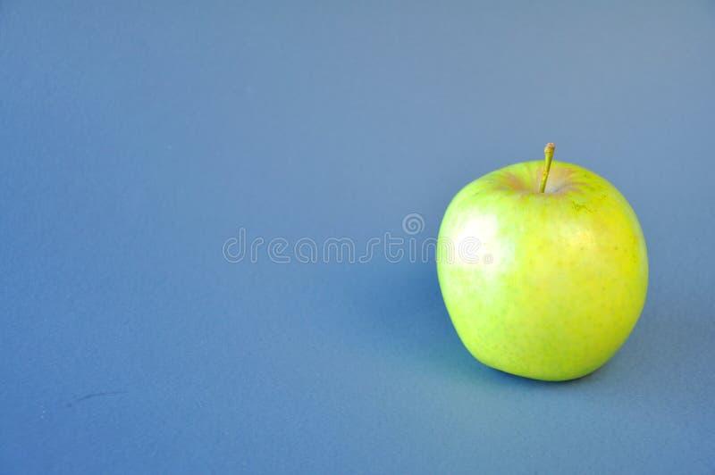 Dojrza?y zielony jab?ko na b??kitnym tle obraz royalty free