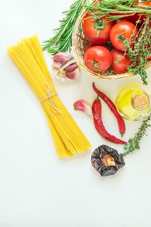 Dojrzałych Organicznie pomidorów ziele Rozmarynowa macierzanka w Łozinowym koszu Spaghetti oliwa z oliwek w butelka Gorących piep fotografia royalty free