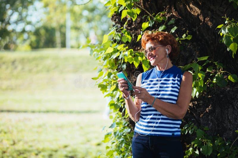Dojrza?a kobieta s?ucha muzyka w parku fotografia stock