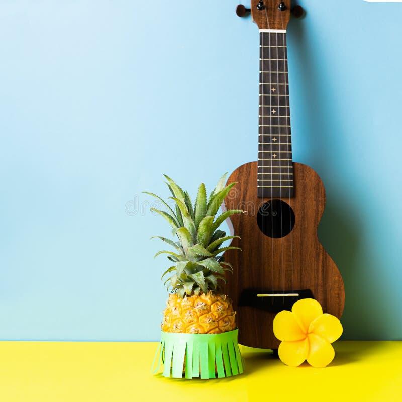 Dojrza?y ananas w zielonej hawajczyk sp?dnicie Ma?ej gitary b??kitny ? fotografia royalty free