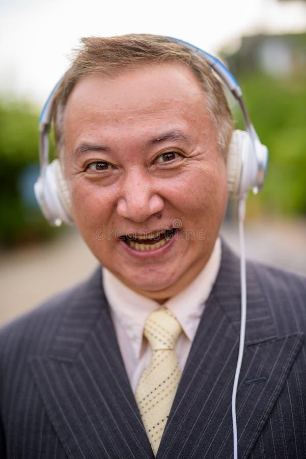 Dojrza?y Azjatycki biznesmen s?ucha muzyka w ulicach przewy?sza zdjęcie royalty free
