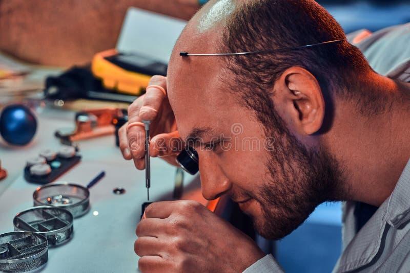 Dojrza?y clockmaster za?atwia starego zegarek dla klienta przy jego ruchliwie naprawianie warsztatem obrazy royalty free