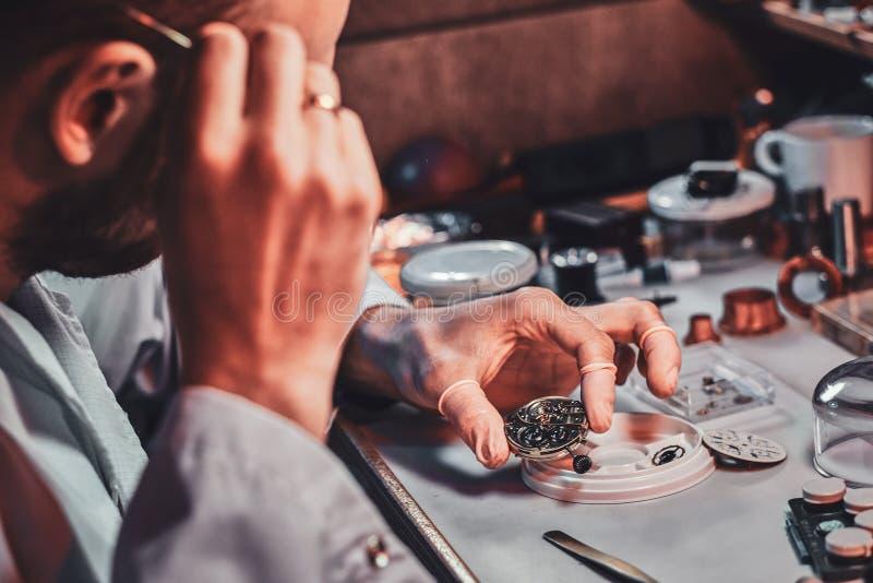 Dojrza?y clockmaster za?atwia starego zegarek dla klienta przy jego ruchliwie naprawianie warsztatem zdjęcia royalty free