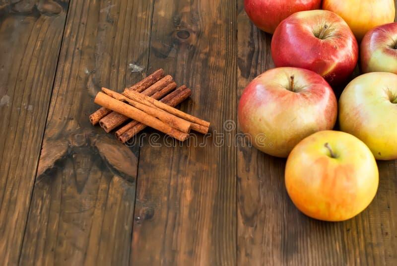 Dojrzali czerwoni jabłka i cynamonowi kije obrazy stock