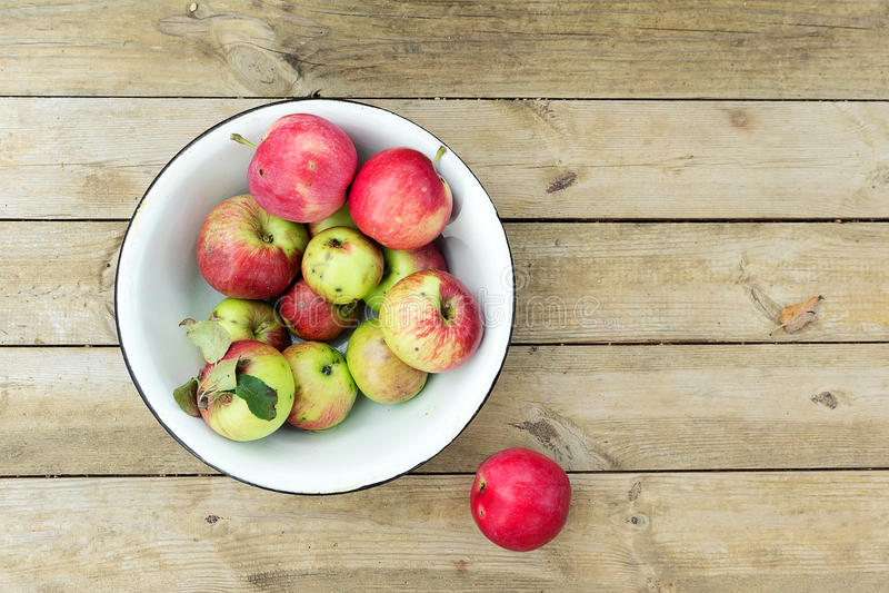 Dojrzali czerwoni jabłka w pucharze na drewnianym tle fotografia royalty free