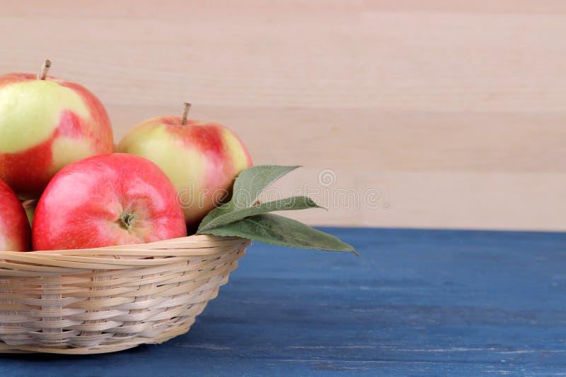 dojrzali czerwoni jabłka z liśćmi w koszu na błękitnym drewnianym stole na tle naturalny drewno z miejscem dla inscriptio i zdjęcie stock