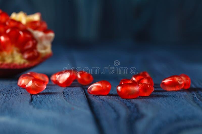 Dojrzali granatowiec czerwieni i plasterka garnet owoc ziarna na stole Sele obrazy royalty free