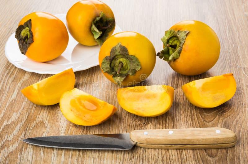 Dojrzali persimmons w talerzu, kawałki persimmon i kuchenny nóż, obrazy royalty free