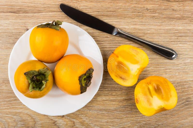 Dojrzali persimmons w talerzu, kawałki persimmon i nóż, zdjęcia royalty free