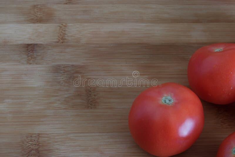 Dojrzali pomidory w górę drewnianego tła dalej, obraz stock
