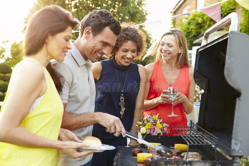 Dojrzali przyjaciele Cieszy się Plenerowego lato grilla W ogródzie fotografia royalty free