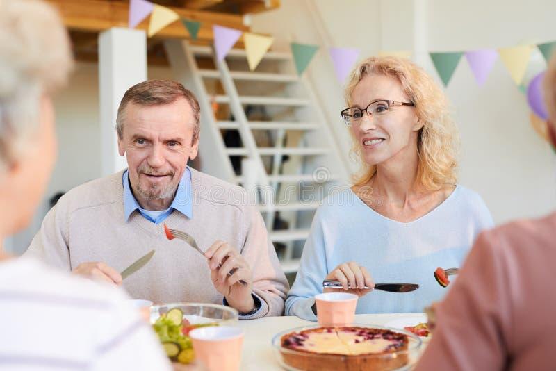 Dojrzali przyjaciele dyskutuje wiadomość przy obiadowym przyjęciem obrazy royalty free