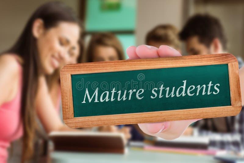Dojrzali ucznie przeciw uśmiechniętym przyjaciołom siedzi studiowanie i używa pastylka komputer osobistego obraz stock