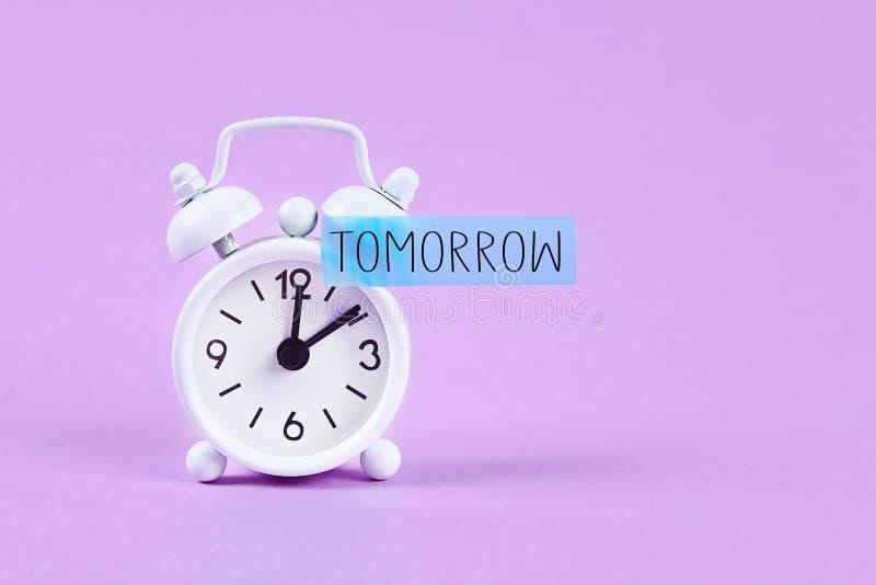 Dojutrkostwo, opóźnienie, pilności pojęcie Biały budzik z kleistą notatką z tekstem jutro zdjęcie royalty free