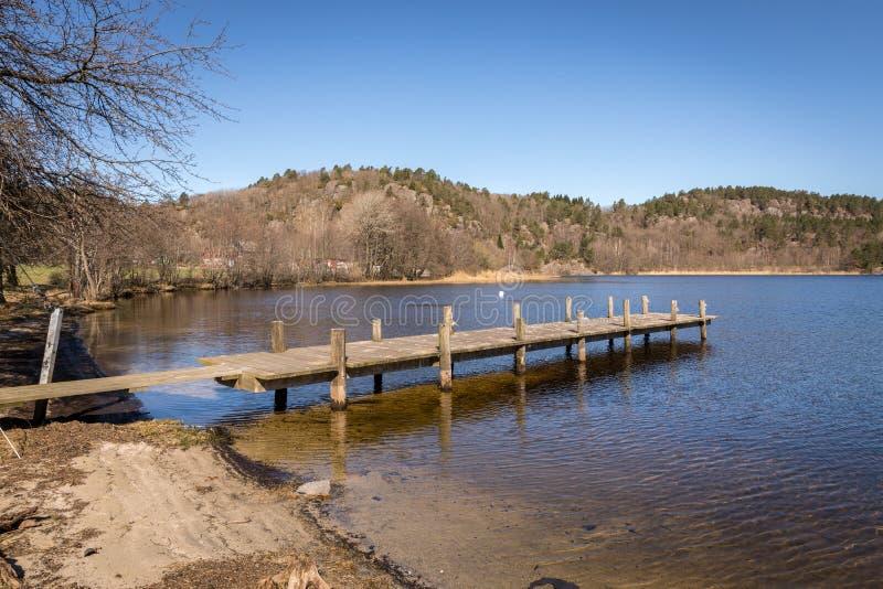 Dok door het meer in Noorwegen, de vroege lente in Tjomsevannet in Sogne stock foto's