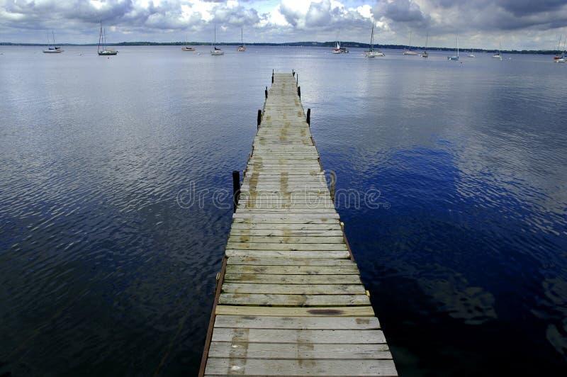Dok het Drijven in Blauw Water stock afbeeldingen