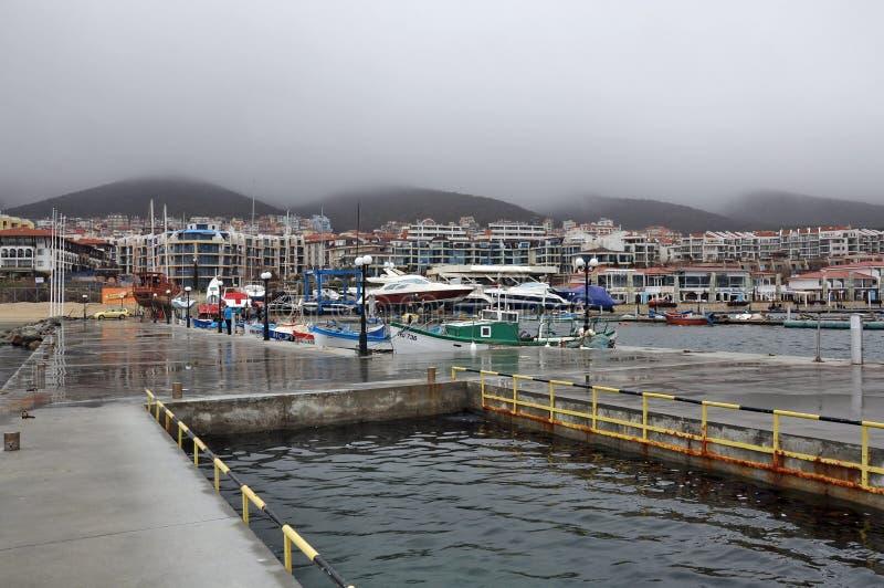 Dok voor boten en jachten, stad, berg, mist stock afbeeldingen