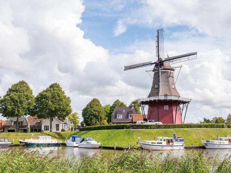 Canal and windmill on fortifications of fortified town of Dokkum, Friesland, Netherlands. DOKKUM, NETHERLANDS - SEP 7, 2017: Motorboats on canal and windmill on stock images