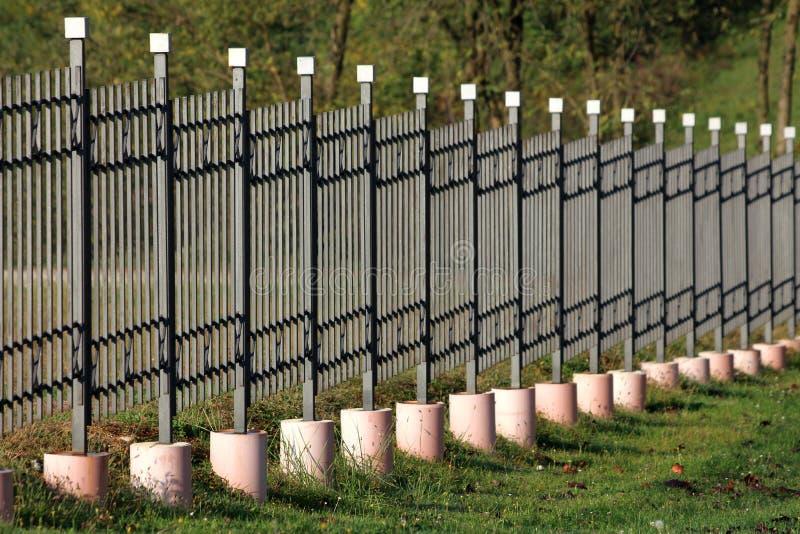 Dokonanego żelaza ogrodzenie z pionowo popielatymi metali barami wspinającymi się na betonowej podstawie otaczającej z trawą i sp zdjęcia royalty free