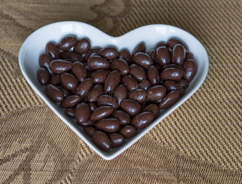 Dokrętki układać w kierowym kształcie na tle Karmowy wizerunek zamknięty w górę cukierku, czekoladowy mleko, ekstre ciemne migdał obraz stock