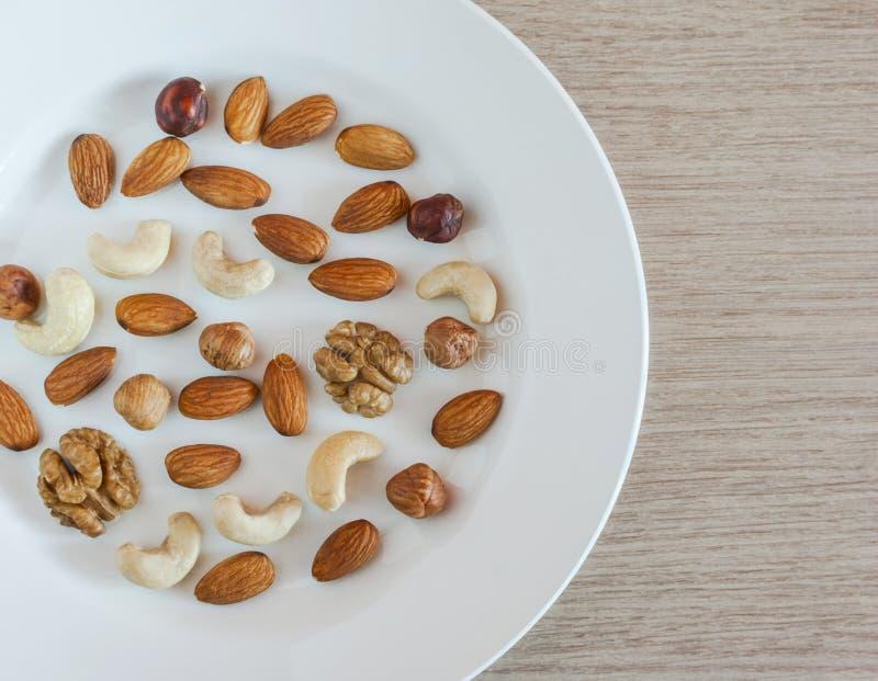 Dokrętki, migdały, Hazelnuts, orzechy włoscy, nerkodrzew dokrętki Na bielu talerzu Na Drewnianym stole Zdrowa Organicznie przekąs zdjęcie royalty free
