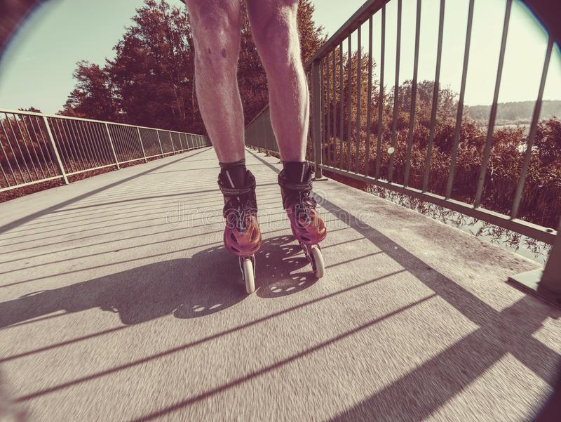 Fit man roller skates riding outdoors on sea bridge royalty free stock photos