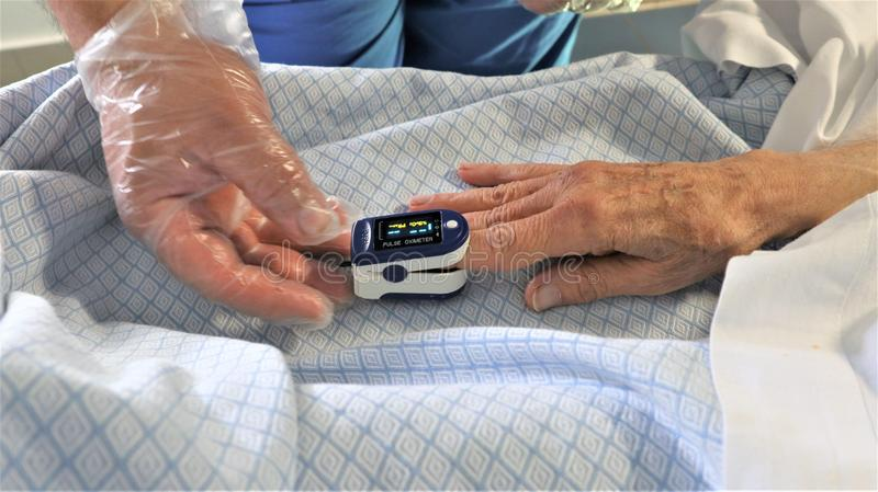 Dokter en geduldige gebruikende oximeter van de vingerimpuls royalty-vrije stock fotografie