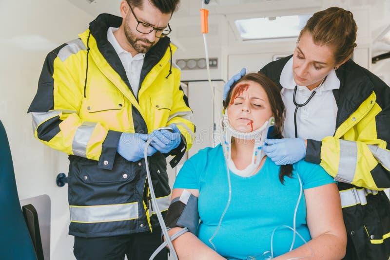Dokters die geharde vrouw in ziekenwagen behandelen stock fotografie