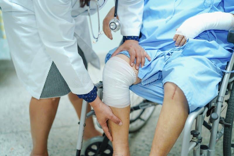 Doktor überprüfen Knie mit Verband auf Rollstuhl, asiatischem geduldigem Unfall älterer oder älterer Frau alter Dame in Pflegekra stockfoto