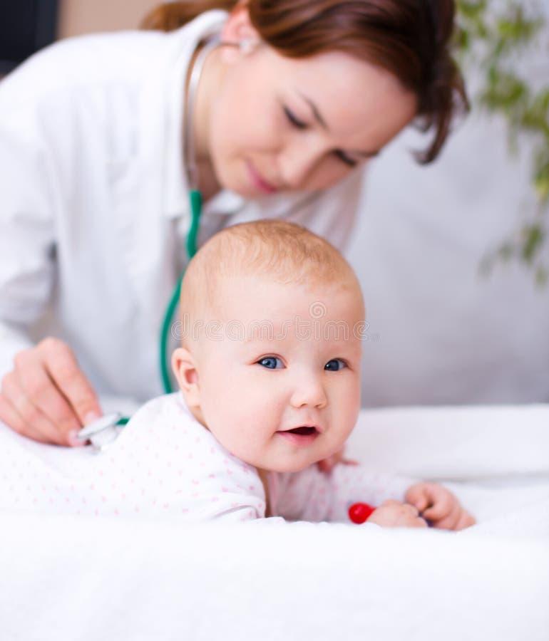 Doktor überprüft kleines Kind lizenzfreie stockbilder