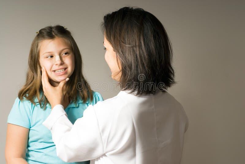 doktor bada twarzy dziewczyny jest poziomy obrazy stock