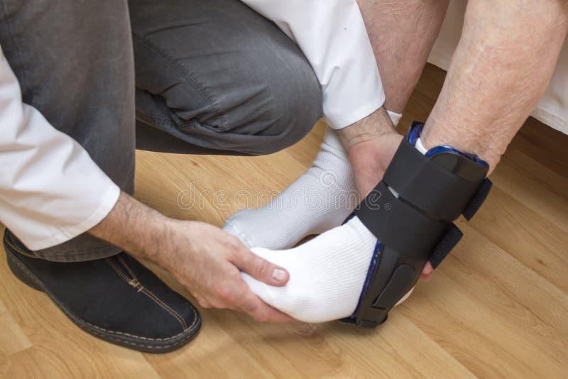 Doktor Bandaging Man Ankle Sätta stabilisatorn på ankeln av en gammal kvinna arkivbilder