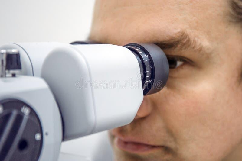 Doktor betrachtet medizinisches ophthalmological Gerät nach der Prüfung des Sehvermögens stockfotografie