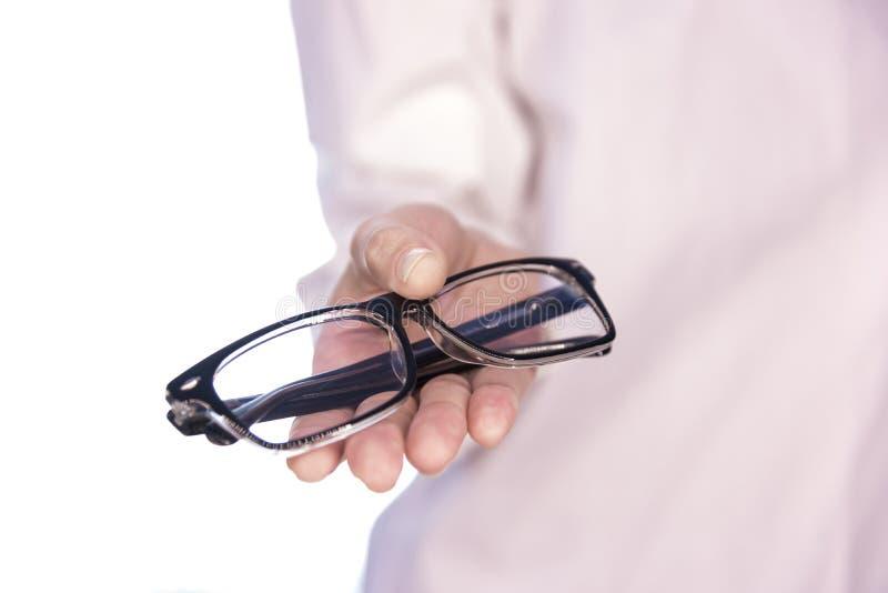 Doktor bietet Gläser für Anblick an stockfotografie