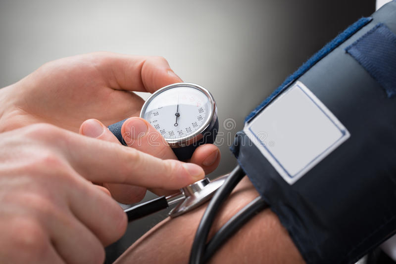Doktor Checking Blood Pressure av en patient royaltyfria foton