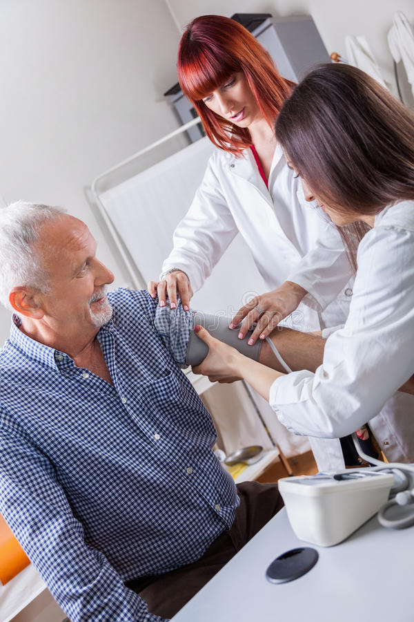 Doktor Checking Blood Pressure till en patient royaltyfri bild