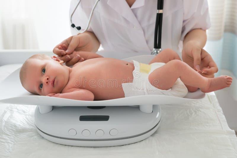 Doktor Checking Weight Of behandla som ett barn royaltyfri fotografi