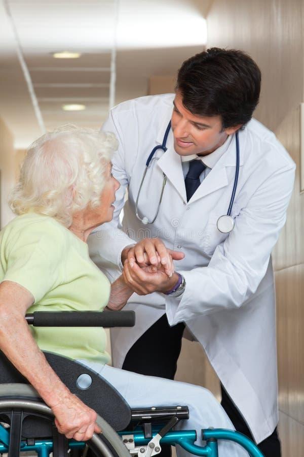 Doktor Comforting Senior Patient på sjukhuset royaltyfri bild