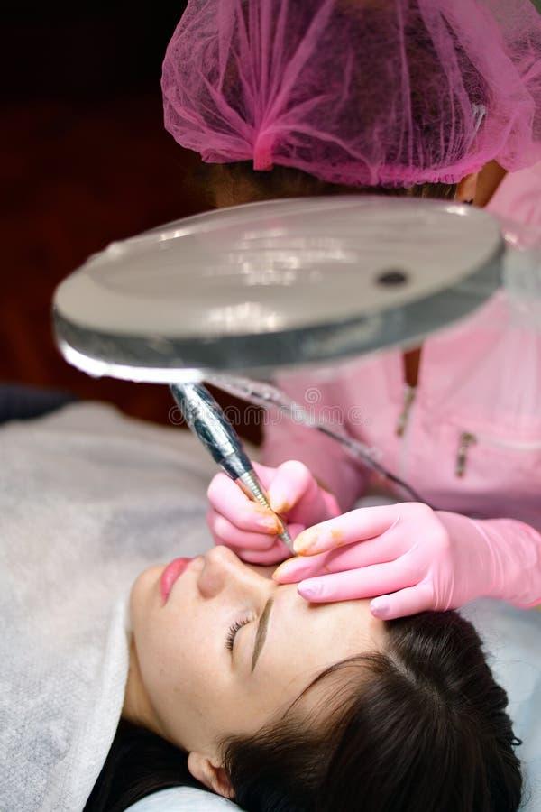 Doktor Cosmetologist, der instrumentellen Farbton von Augenbrauen tut lizenzfreie stockfotos