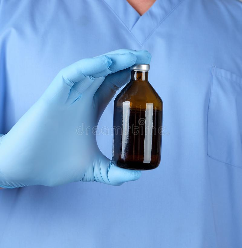 Doktor in den blauen Uniform- und Latexhandschuhen, die eine braune Glasflasche mit Medizin für Behandlung halten lizenzfreie stockbilder
