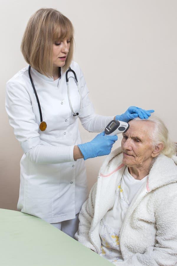 Doktor in den Wegwerfhandschuhen überprüft eine alte Frau Messen der Temperatur mit einem Laser-Thermometer lizenzfreies stockfoto