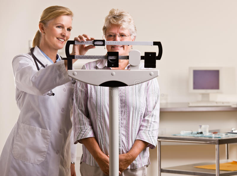 Doktor, der ältere Frau im Doktorbüro wiegt lizenzfreie stockbilder
